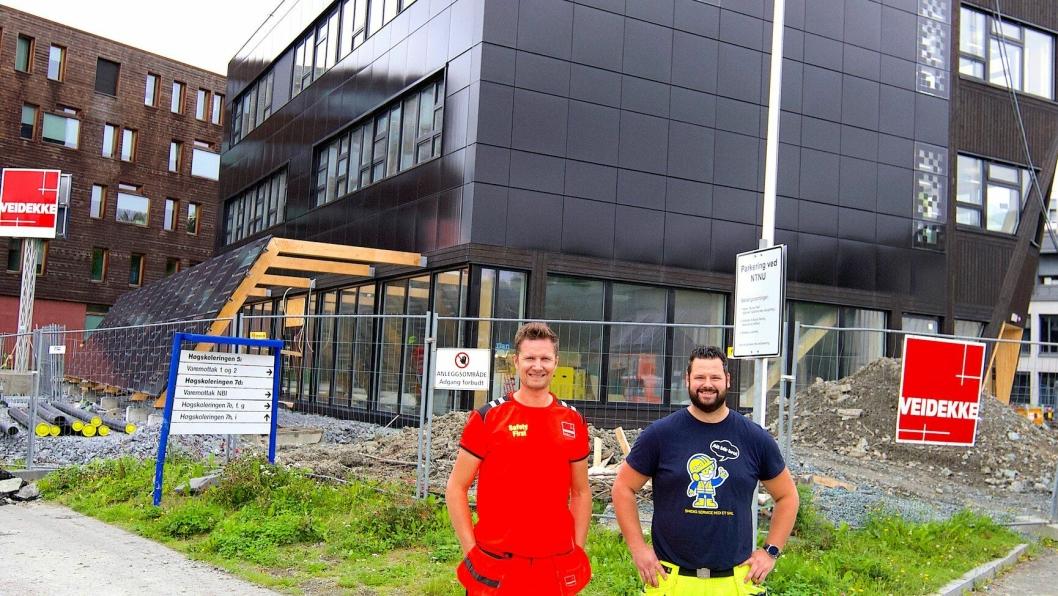 PILOT-PROSJEKT: Ramirents hovedansvarlige for byggestrøm i Trøndelag, Andrew Steven Tuck (t.h.) og driftsleder i Veidekke, Rickard Tällberg foran ZEB-laboratoriet der energi fra solcelleanlegget benyttes til byggestrøm.