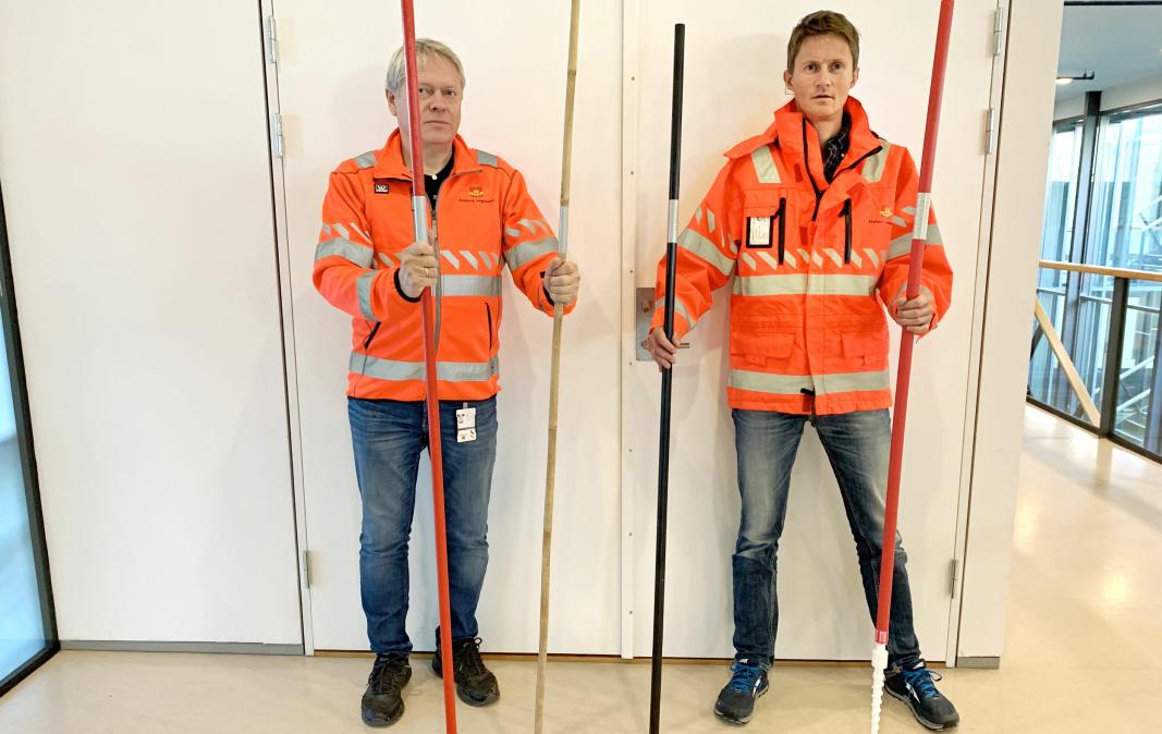 Øystein Larsen (t.v.) og Bård Nonstad viser noen av brøytestikkene som blir med i testen i vinter. Fra venstre: rødmalt furu, bambus, svartmalt furu og rød plast skrubrøytestikke.