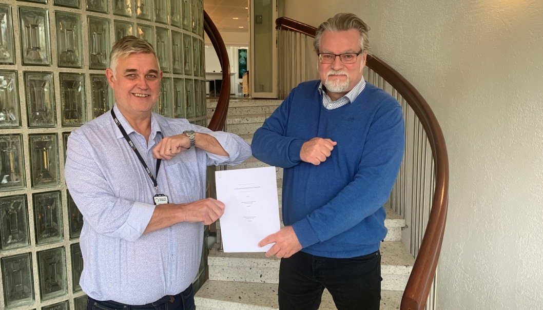Med «korona- håndtrykk» mellom Arild Nybø (t.v.) og Roar Sømoen, inngås avtale om salg av NKR til Sentralregisteret.