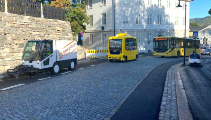 Feierobot sammen med buss, selvkjørende buss og vanlig feiemaskin i Kongsberg sentrum.