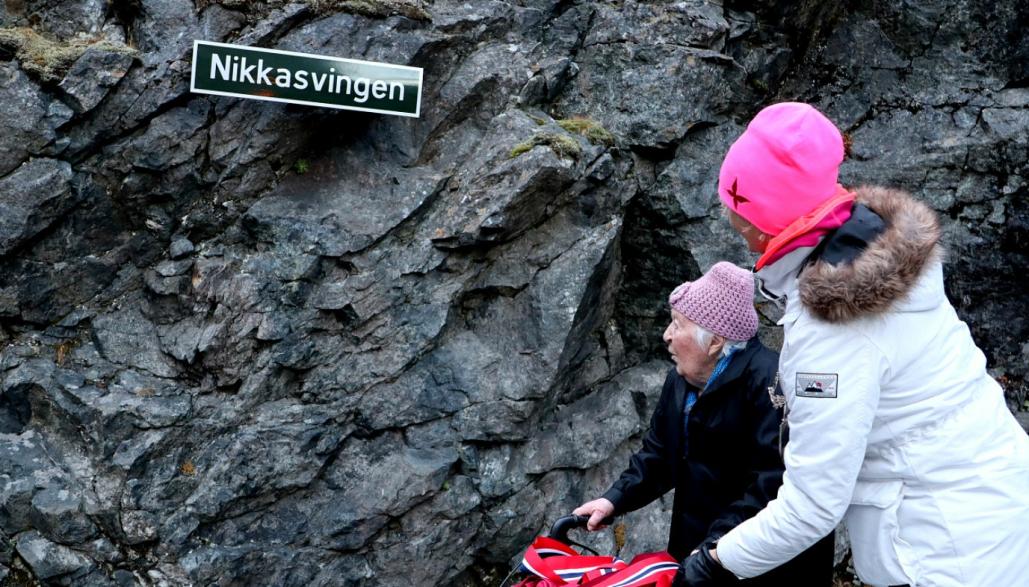 Nikoline Myren Grønning og fylkesordfører Tove-Lise Torve foran skiltet som viser at svingen ved Stigfossen for alltid skal hete Nikkasvingen, til ære for henne og de andre anleggskokkene som var med og bygget Trollstigen.