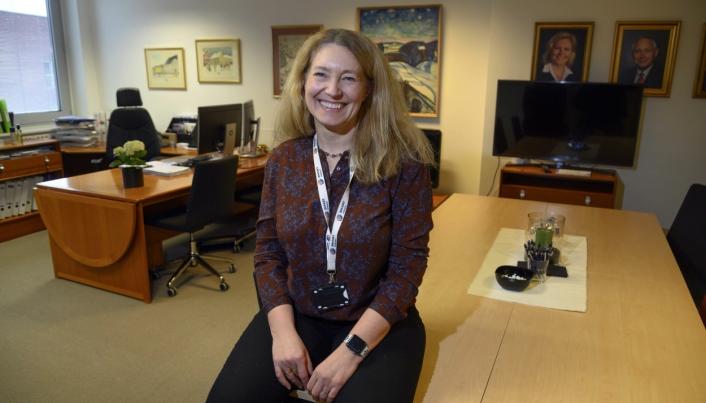 Tone Lindberg Grøstad på kontoret med forgjengere på veggen bak. Foto: Espen Braata