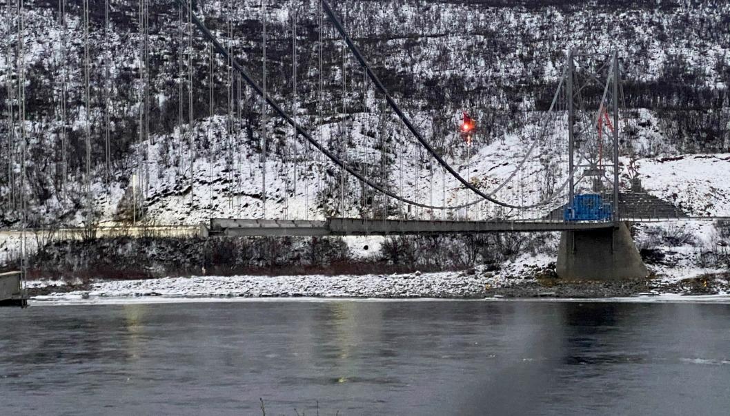 ALADDIN: Nærmest som et flyvende teppe henger gamle Tana Bru i wirene over den lakserike Tanaelva, mens dekket og stålet i sidene ble fjernet meter for meter uten at noe måtte havne i elva. Løpekatten lyser rødt i lufta.