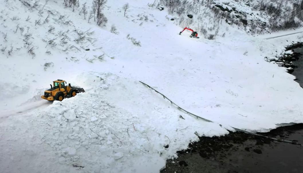 En hjullaster og en gravemaskin rydder snø på fv. 883 ved Skillefjorden. Like ved rydder en hjullaster og en gravemaskin et annet snøras. Autovernet har lite å stå imot naturkreftene med.
