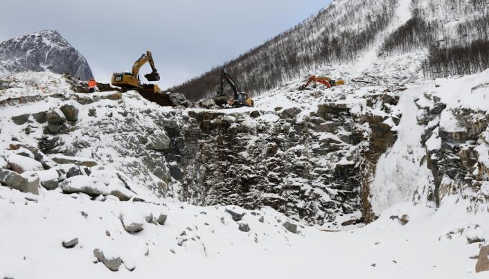 HEFTIG: En rekke maskiner er satt på jobben med å bygge et nytt led for kommende skred. Til venstre er den kjente fjelltoppen Segla som tusenvis av turister puster og peser seg til toppen av hvert år. Foto: Klaus Eriksen