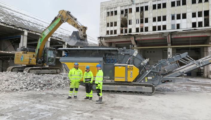 STRIPPET: Anleggsleder Ove Odden (f.v.), avdelingsleder Agnar Haugen og maskinsjef Torbjørn Haugo foran et av de strippede betongbyggene som snart blir knust masse. Foto: Bjørn E. Eriksen