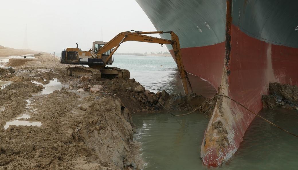 En ikke altfor stor graver er satt i arbeid for å prøve å få løs det grunnstøtte containerskipet i Suezkanalen. (Se bilde av hvor stort skipet er i forhold til graveren nedenfor).
