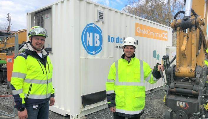 NCCs områdesjef i Oslo Svein Nilsplass (t.v.) og Jannik Stanger i EST Nordic tester ut hurtiglading fra en mobil 390 kWh batteribank for de av helelektriske anleggsmaskinene under byggingen av ny sykkelvei i Enebakkveien i Oslo.