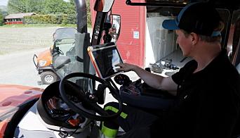 TRYKKER TIL: - Jeg elsker gadgets, sier Petter Pilgaard og går løs på den store skjermen i hytta på Kubota-traktoren. Foto: Klaus Eriksen