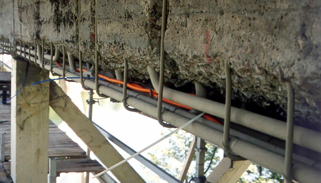 Drager på undersiden av en bro er klargjort for montering av forskaling for utstøping med ny mørtel. Den eksisterende konstruksjonen er meislet, dårlig betong er fjernet, og armeringen er rengjort og påført korrosjonsbeskyttelse.